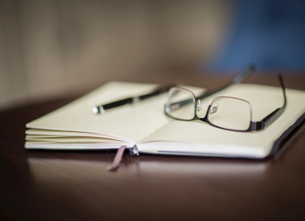 notepad with pen and glasses