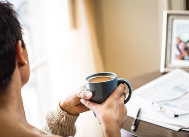woman holding a cup of tea and looking out a window