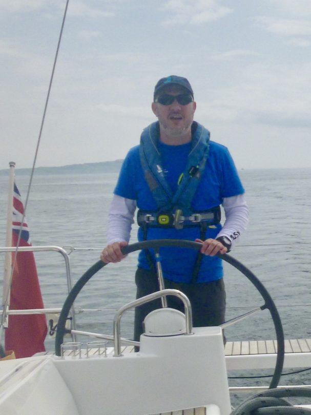 Colin McAdam steering a boat