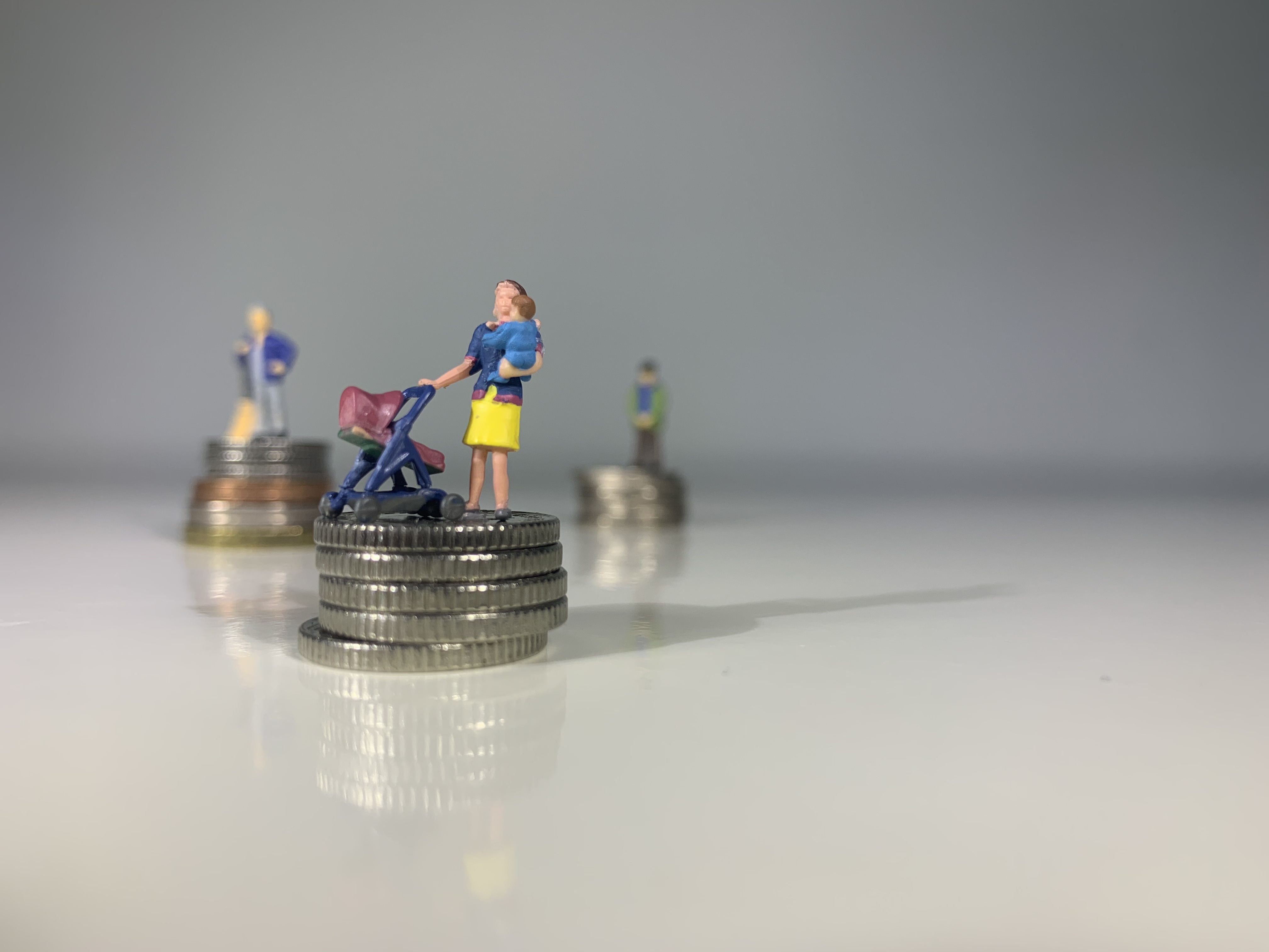 little people standing on stacks of coins