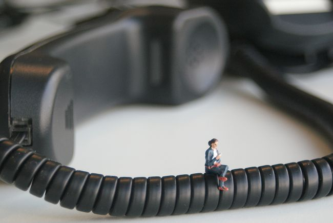 Small model figure sitting on telephone handset cable