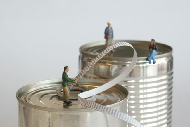 Small model figures standing on metal food tins