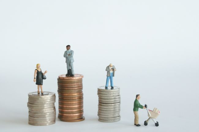 Small model figures standing on stacks of coins