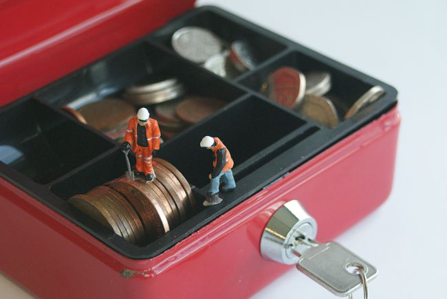 Small model figures working inside a red box with key