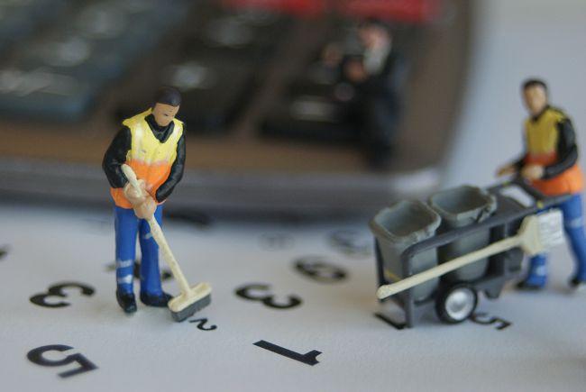 Small model figures dressed as bin men sweeping up numbers