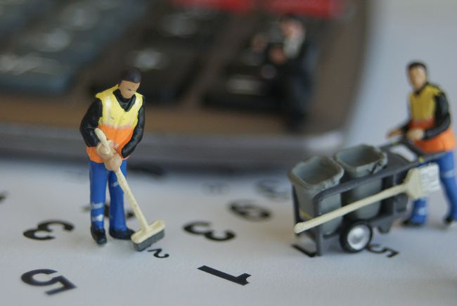 Small model figures dressed as bin men sweeping up numbers