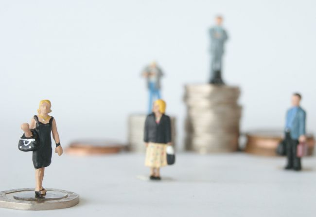 Small model figures walking past stacks of coins