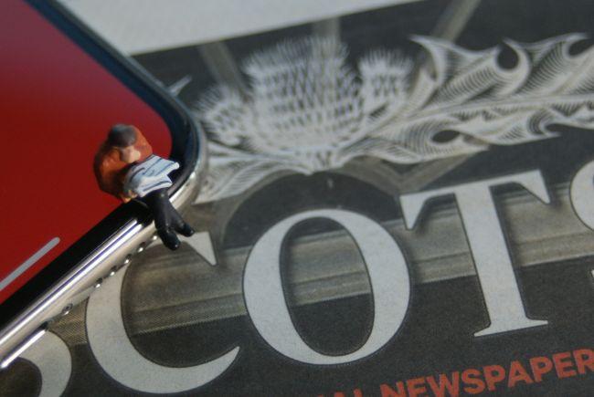 Small model figure sitting beside a newspaper