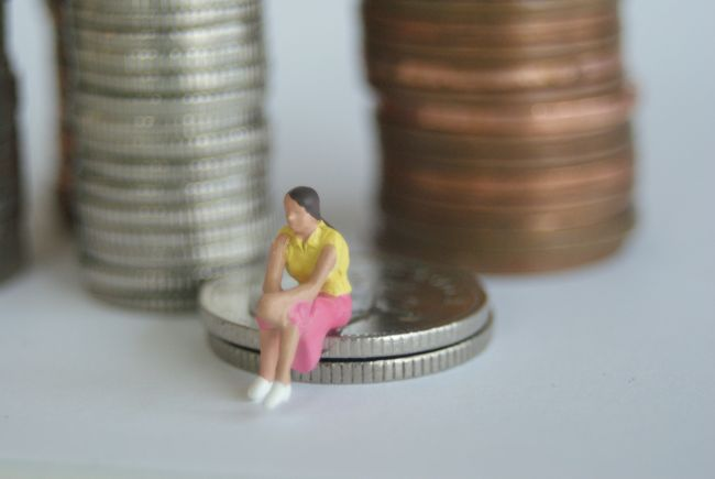 Small model figure sitting beside large pile of coins