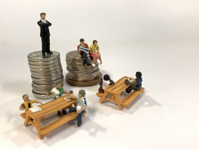 small model figures sitting on benches beside a stack of coins