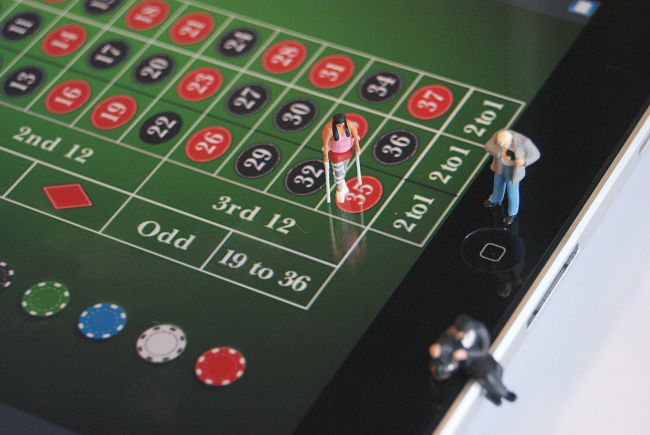 Small model figures standing on casino game table