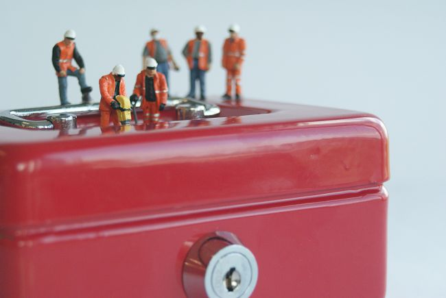 Small model figures standing on locked red box