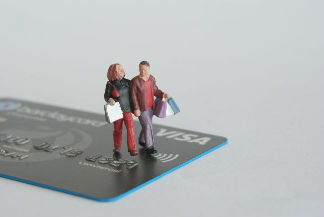 Small model figures walking across a credit card