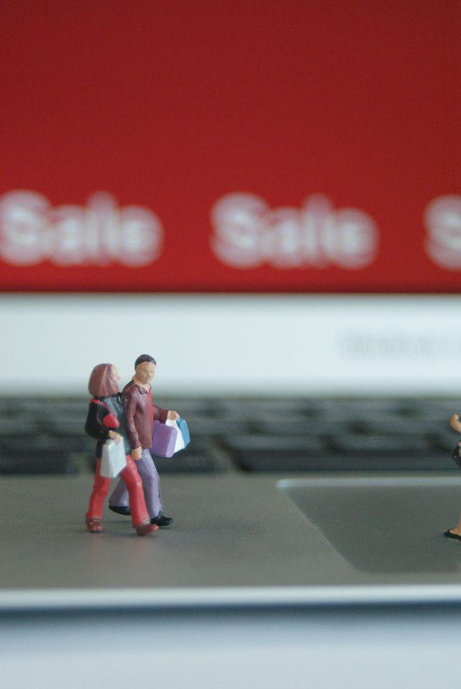 Small model figures walking across laptop keyboard