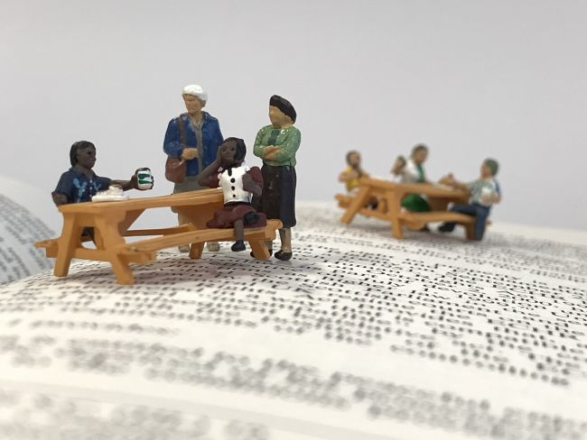 small model figures sitting on benches