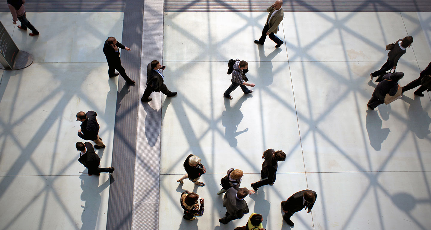 View from above of commuters crossing building interior