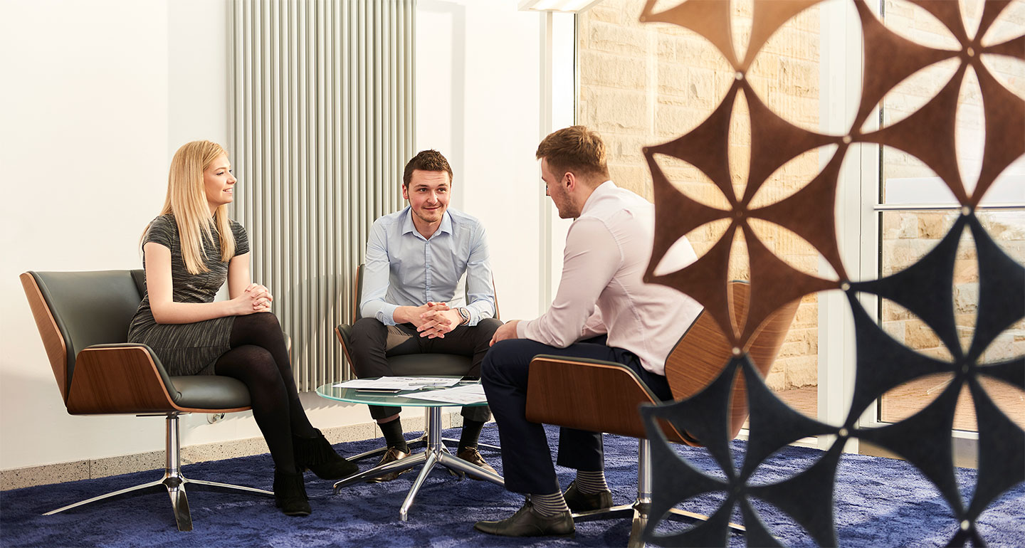 Young people sitting in modern office talking