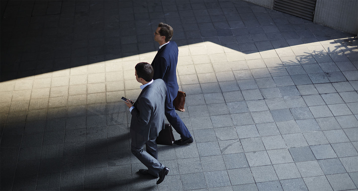 Two businessmen walking across a tiled floor