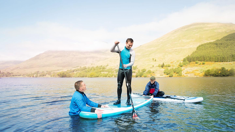 Three men paddleboarding