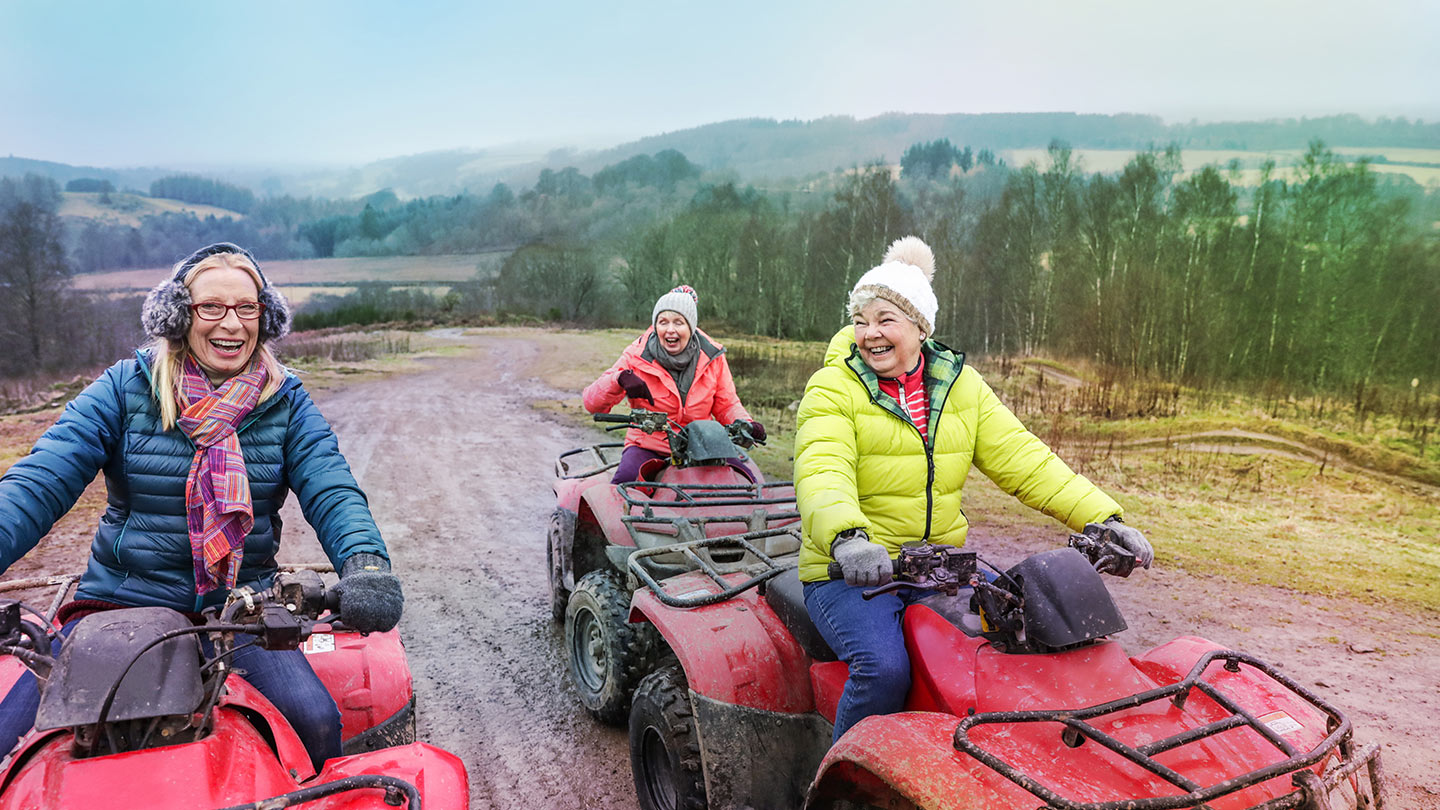 Three retired women riding on quad bikes