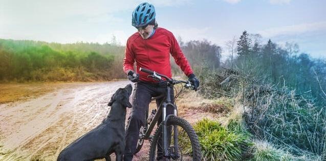 cyclist and his a black labrador