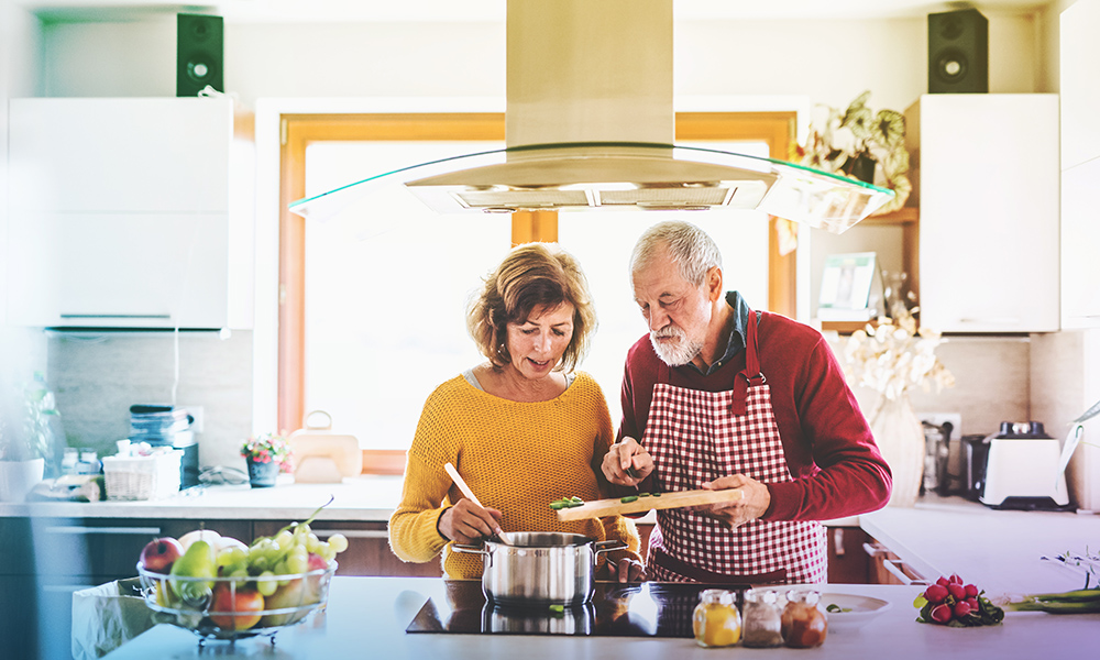 Couple cooking together in a bright kitchen