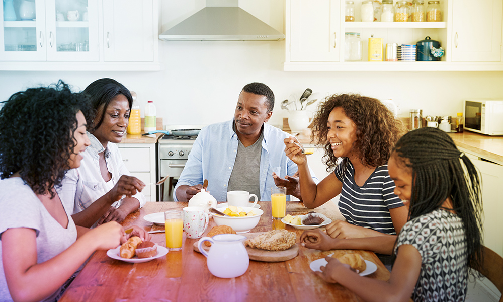 Happy family eating breakfast together