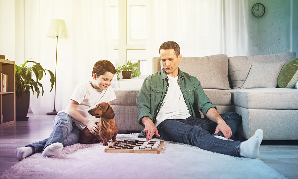 Father and son relaxing on floor playing draughts with family dog