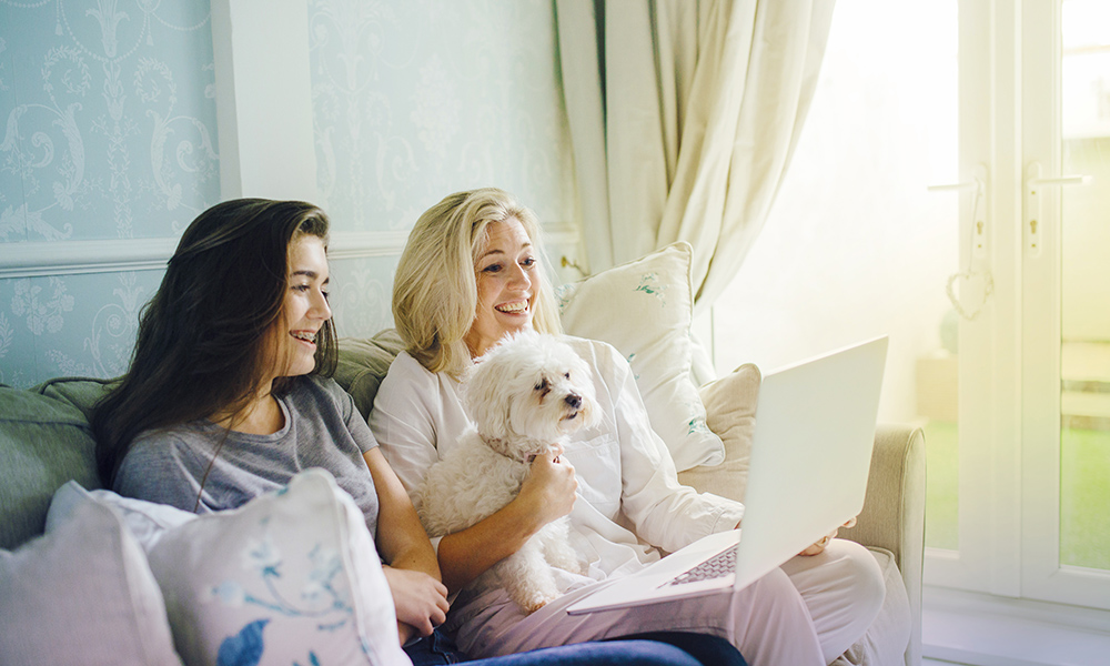 Mother and daughter on sofa smiling and looking at laptop with white dog beside them