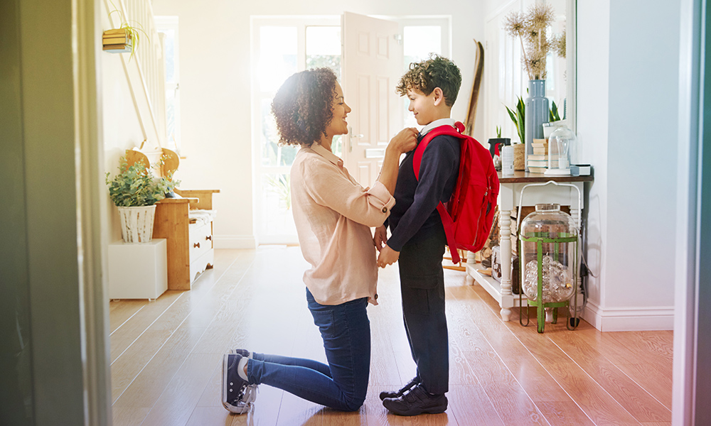 Mother helping son get ready to leave for school