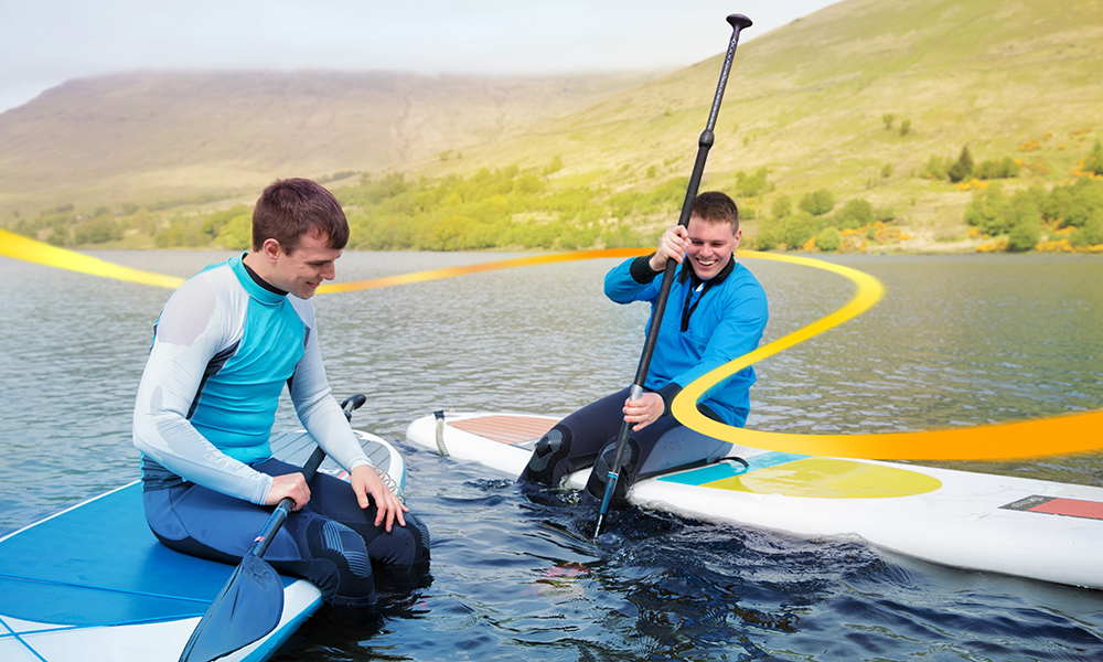 Two men sitting on their paddle boards in conversation