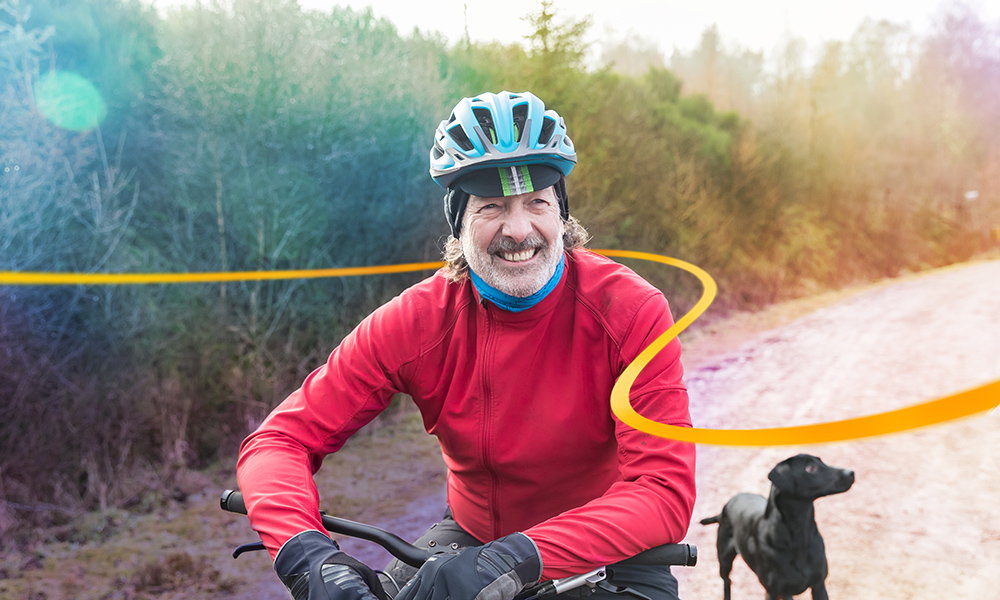 Male cyclist and his black labrador outdoors