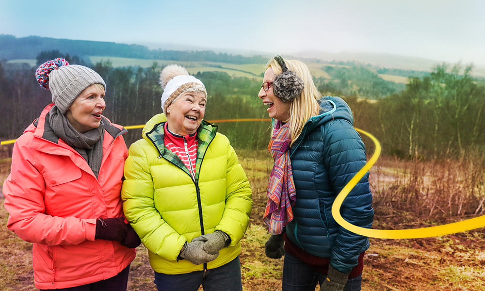 Three women in conversation laughing and enjoying the outdoors
