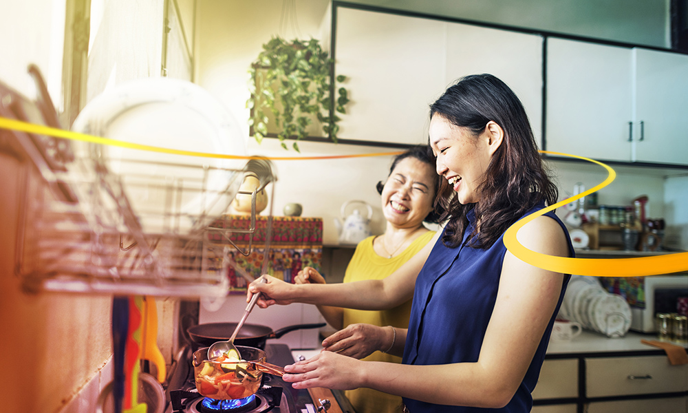 Mother and daughter laughing and enjoying cooking in their kitchen together