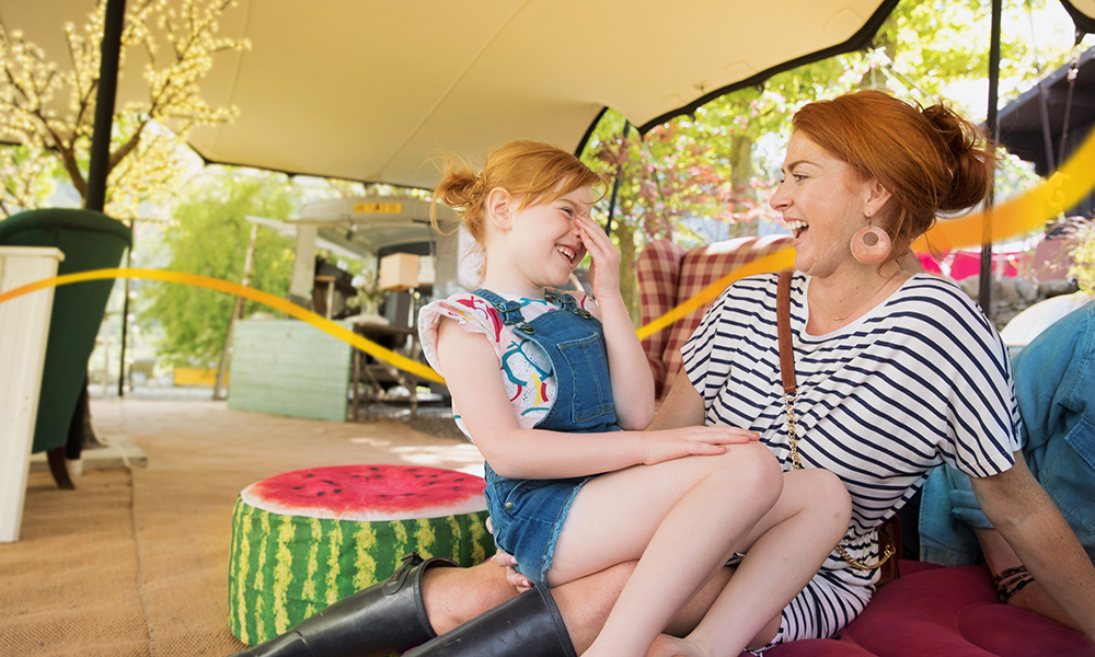 Mother with daughter on her knee outside laughing together