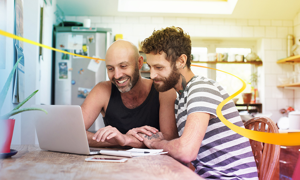 Two men sitting at kitchen table with laptop smiling and laughing