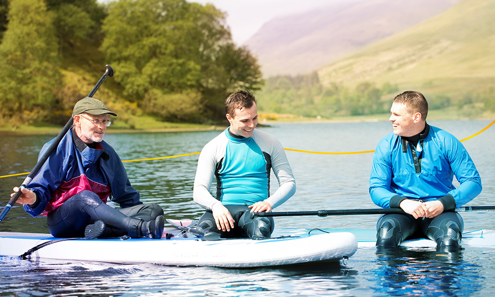 Three men paddle boarding laughing and chatting together