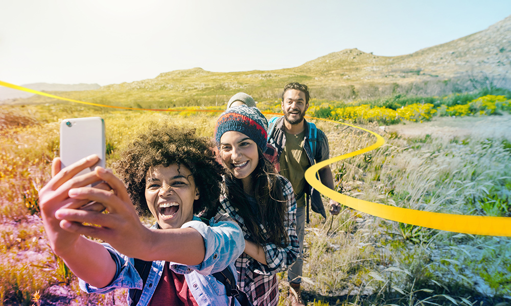 Three happy  friends taking a selfie while out walking in the hills